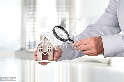 626187670istockphoto Hands with house and magnifying glass, search home concept 653750782