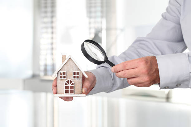 Hands with house and magnifying glass, search home concept stock photo