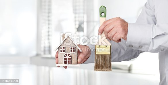 istock Hands with house and paint brush, home services painter concept 816236794