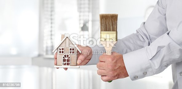 istock Hands with house and paint brush, home services painter concept 816236798