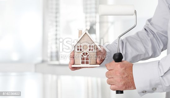 istock Hands with house and paint roller, home services painter concept 816236802