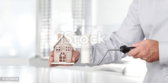 istock Hands with house and paint roller, home services painter concept 816236808