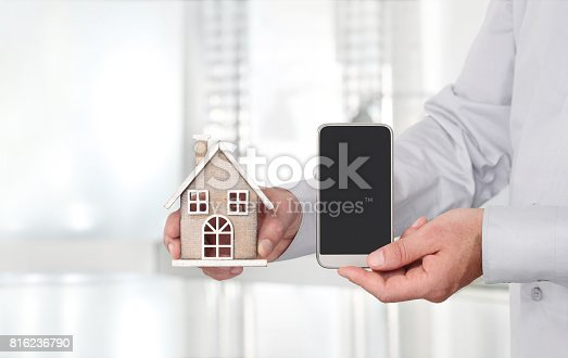 1023041738istockphoto Hands with house and smart phone mobile, advertisement concept 816236790