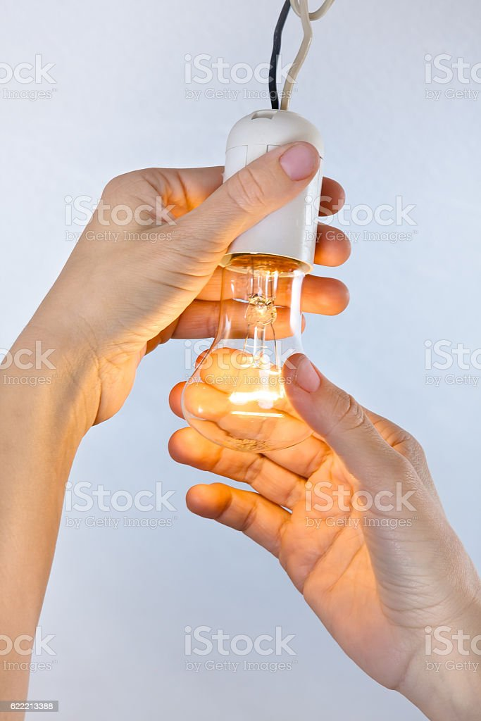 hands with incandescent light bulb stock photo