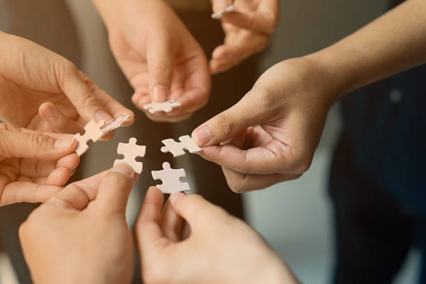 hands with jigsaw join together as team - employee engagement stock photos and pictures