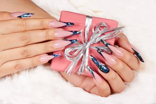hände mit langen künstlichen gepflegten nägel french hält eine geschenkbox mit schleife - nageldesign weihnachten stock-fotos und bilder
