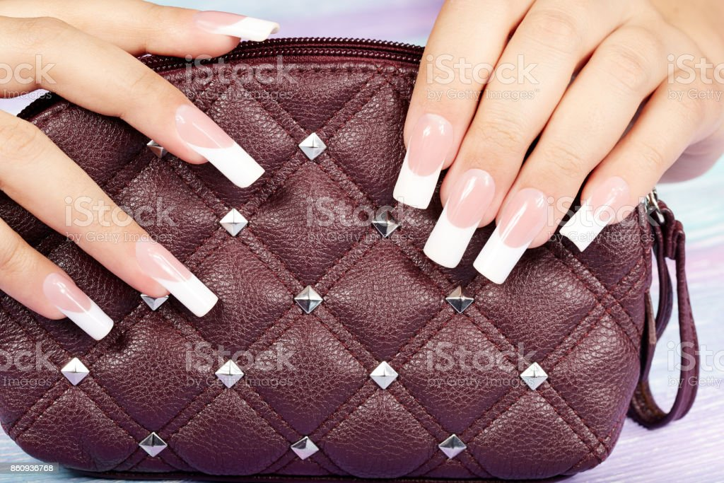 Hands with long artificial french manicured nails holding a handbag