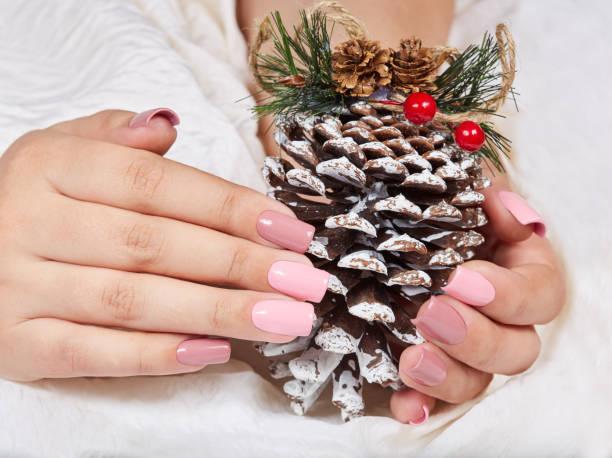 hände mit langen künstlichen rosa gepflegten nägeln hält eine kiefer weihnachtsdekoration - nageldesign weihnachten stock-fotos und bilder
