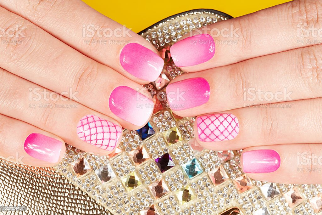 Hands with manicured nails covered with pink nail polish stock photo