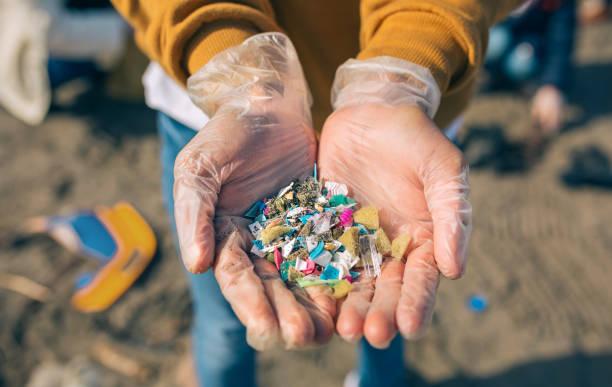 las manos con microplásticos en la playa - contaminación ambiental fotografías e imágenes de stock