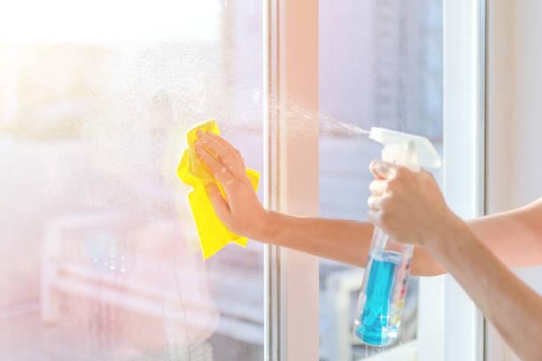 ナプキンのクリーニングウィンドウを持つ手。洗浄スプレーで窓ガラスを洗う - 家事 ストックフォトと画像