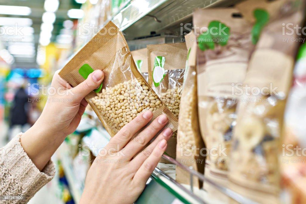 Manos con piñones de envasado en la tienda - foto de stock