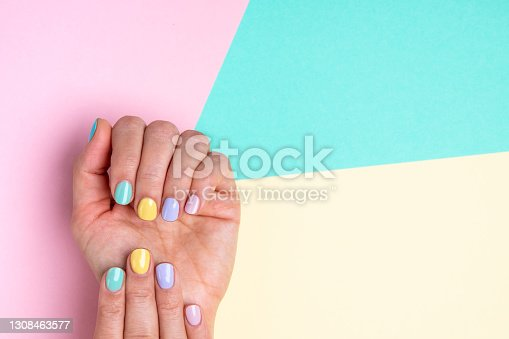 istock Hands with pastel nail polish on multicolored background. 1308463577