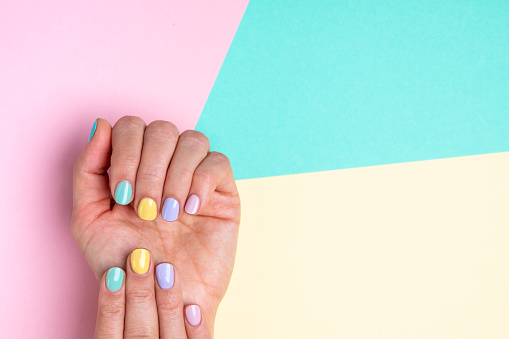 Bright trendy female manicure in funky spring colors. Woman's hands with pastel manicure on yellow, pink and blue background. Beautiful multi colour spring Easter manicure. A lot of space for text.
