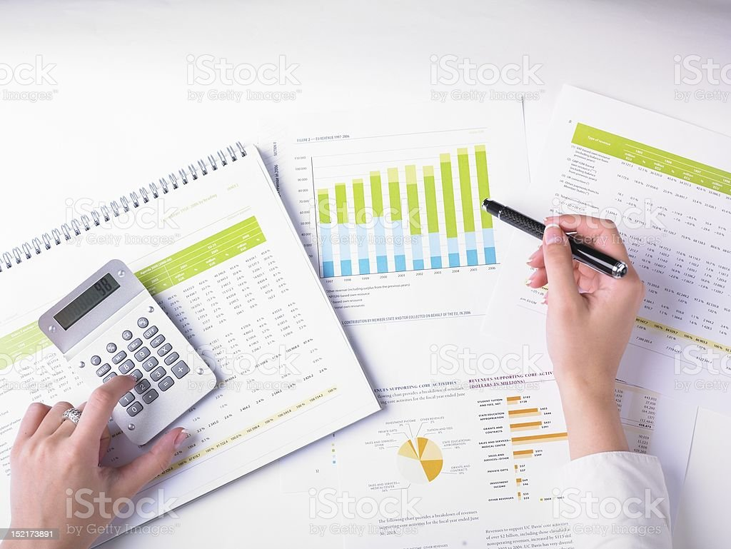 Hands with pen and calculator on colorful charts stock photo