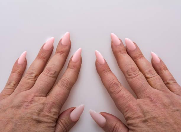 hände mit rosa acryl nägel - nails stiletto stock-fotos und bilder