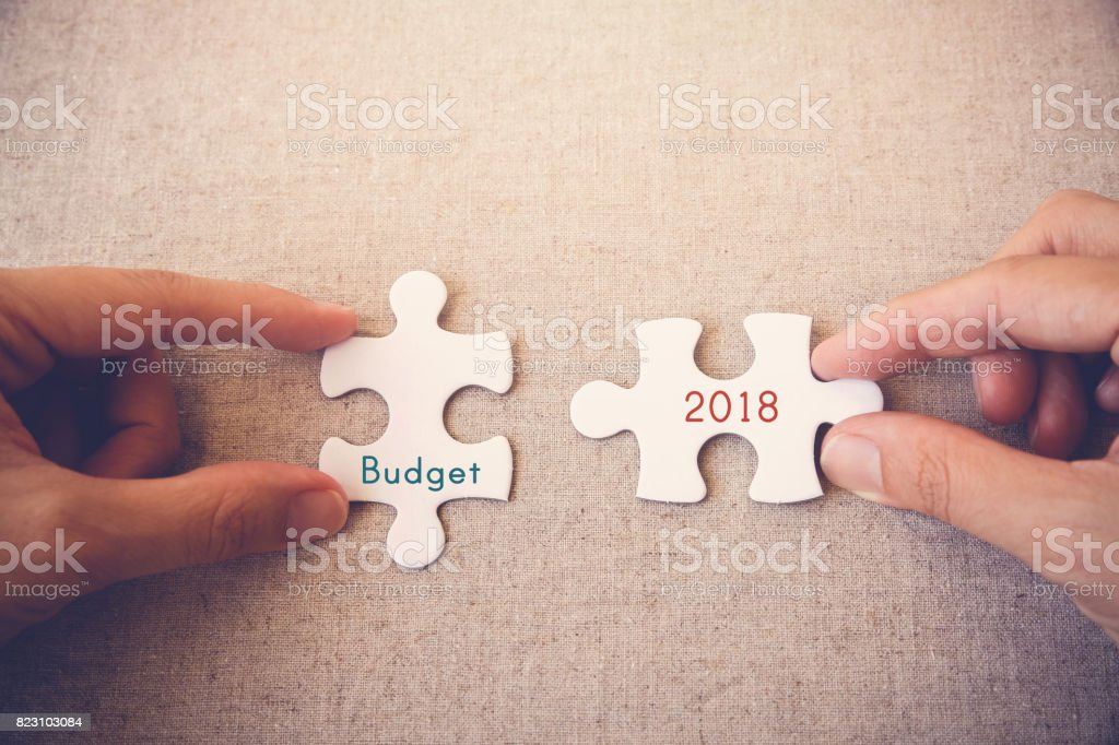 Hands with puzzle pieces and 'budget 2018' words stock photo