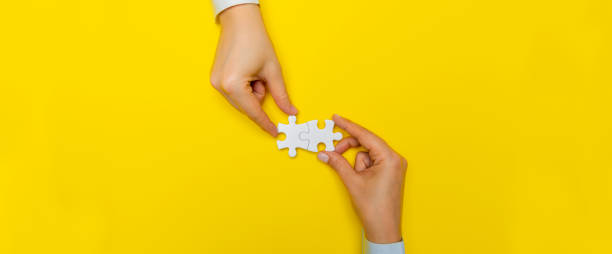 Hands with Puzzle Pieces Business people are merging two puzzle pieces. business stock pictures, royalty-free photos & images