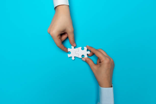 Hands with Puzzle Pieces stock photo