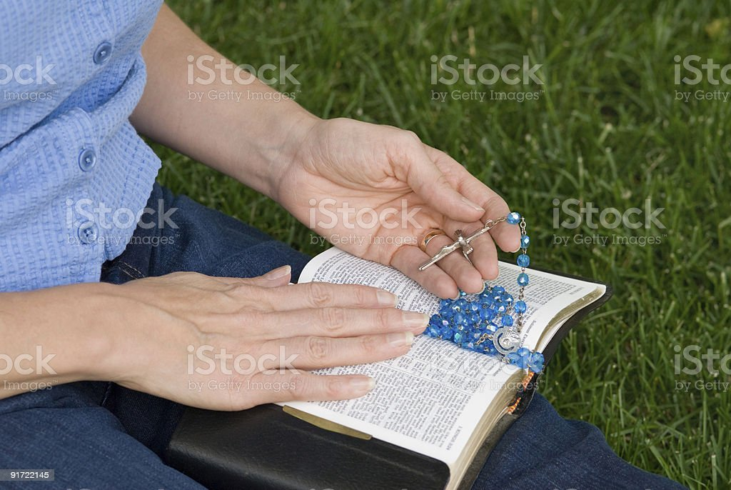 Hands with Rosary on Bible royalty-free stock photo