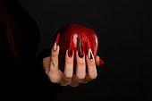 毒赤リンゴを保持怖い爪のマニキュアが付いている手