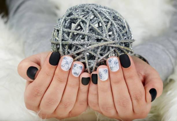 hände mit kurzen gepflegten nägeln gefärbt mit schwarzen und weißen nagellack - nageldesign weihnachten stock-fotos und bilder