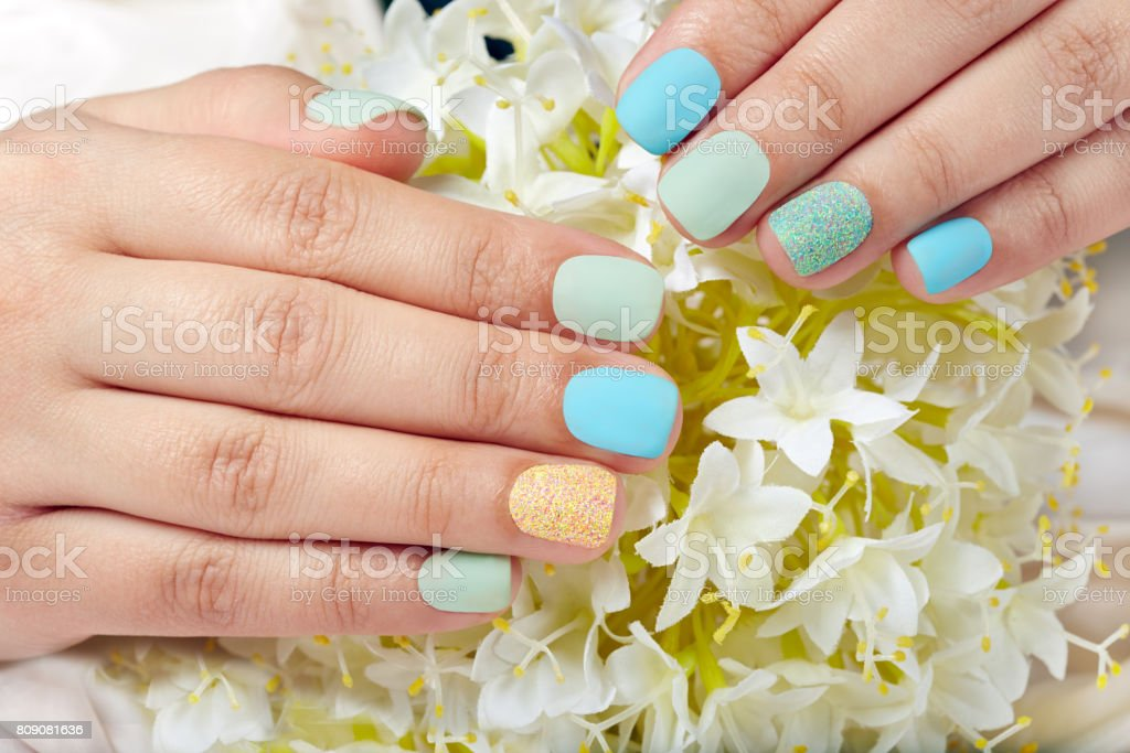 Hands with short matte manicured nails and white flowers
