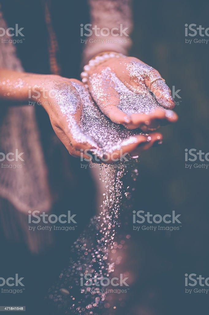 Mãos com glitter prata caindo de - - foto de acervo