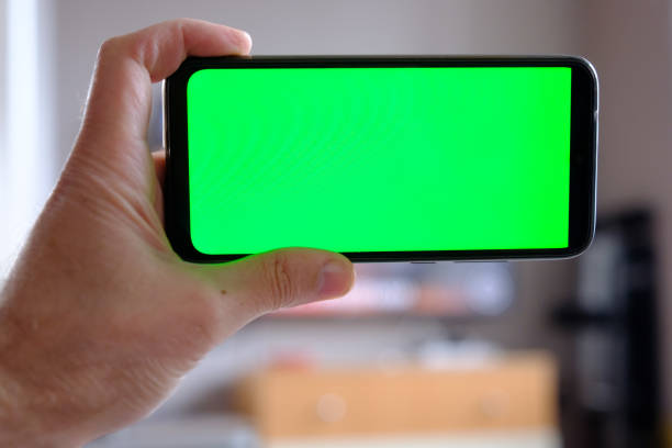 Hands with smartphone, green chroma key stock photo