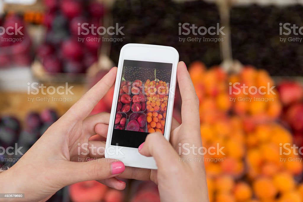 hands with smartphone taking picture of fruits stock photo