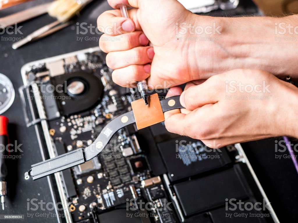 Hands With Thermal Paste Applying It To The Computer Laptop