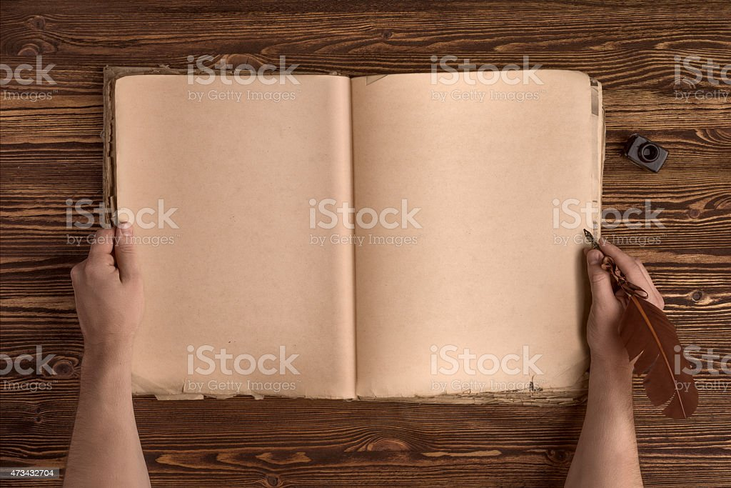 hands with vintage quill pen, old book on wooden table stock photo