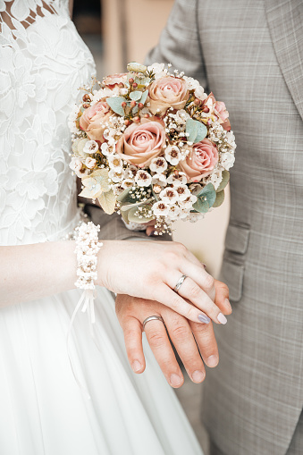 Hands with wedding rings and a flower bouquet