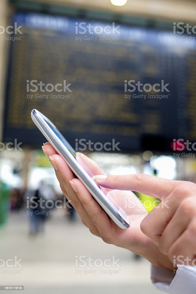 Hands woman using her cell phone in train station stock photo