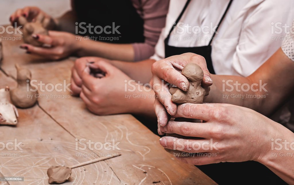 hands working and finishing sculpture with clay on wooden table in workshop stock photo