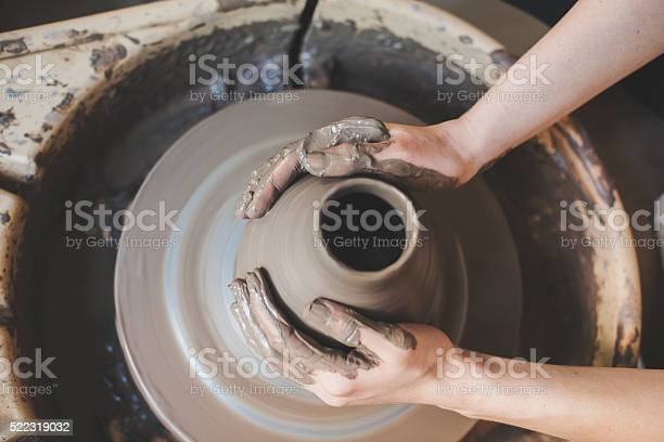 Human hands working on pottery wheel, close up