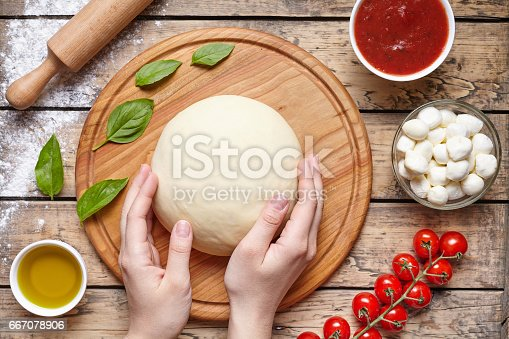 1136817041 istock photo Hands working with dough preparation pizza or pie making ingridients, food flat lay on kitchen table background. Dough, mozzarella cheese, tomatoes sauce, basil, olive oil or bakery cooking. 667078906