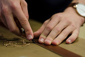 Hands working with leather for handicrafts, close up