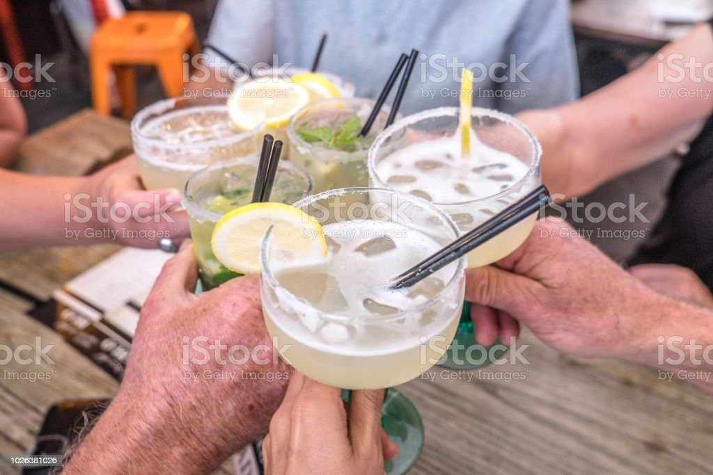 Hands young and old celebrating making a toast and clinking cocktail glasses with margaritas and mojito drinks at celebration stock photo
