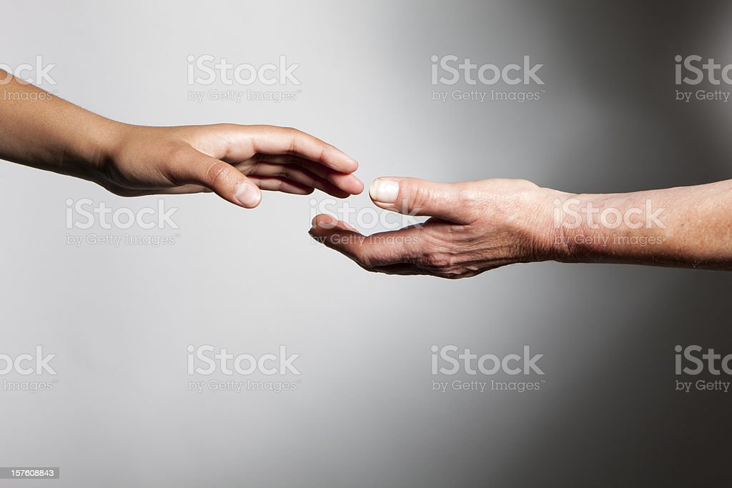 hands: young and old hands reaching out to each other stock photo