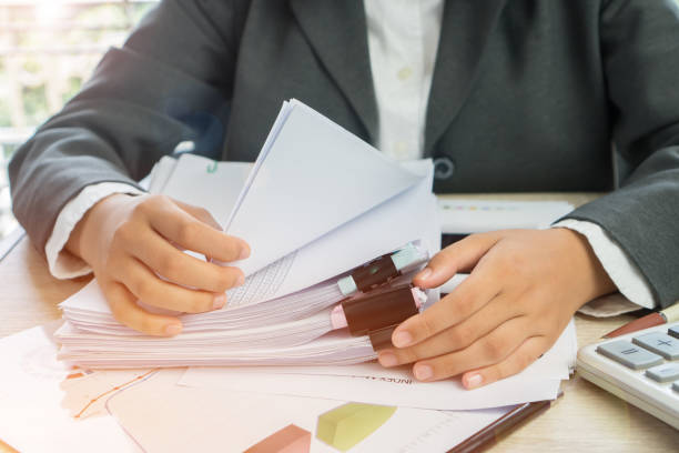 Hands young female business managers checking and arranging stack of unfinished documents reports papers for result graph marketing, startup project for plan job succes in Busy office with flare light stock photo