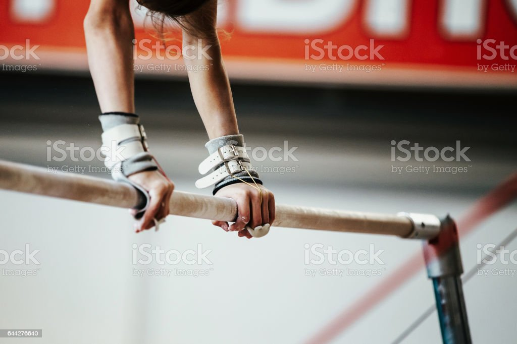 hands young girl gymnast exercise on uneven bars stock photo