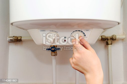 996279800istockphoto Hands young women set the temperature of the water in the electric boiler. 1140851801