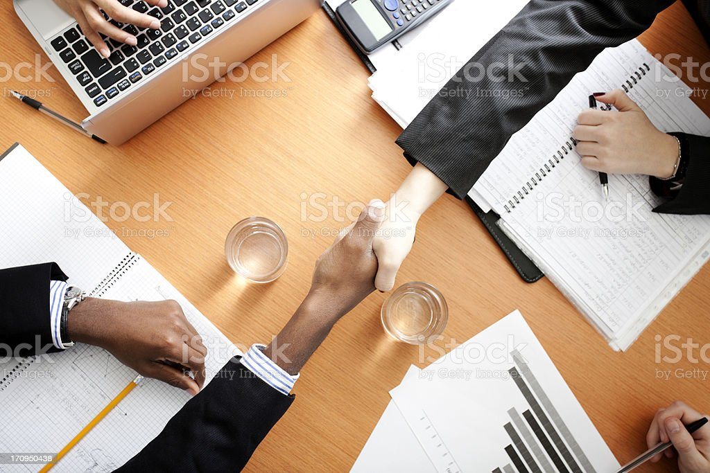 Handshake across the table royalty-free stock photo
