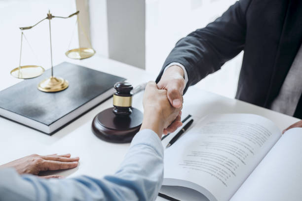 Handshake after good cooperation, Businesswoman Shaking hands with Professional male lawyer after discussing good deal of contract in courtroom, Concepts of law, Judge gavel with scales of justice stock photo