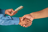 istock Handshake And Giving Money Background 1186111710