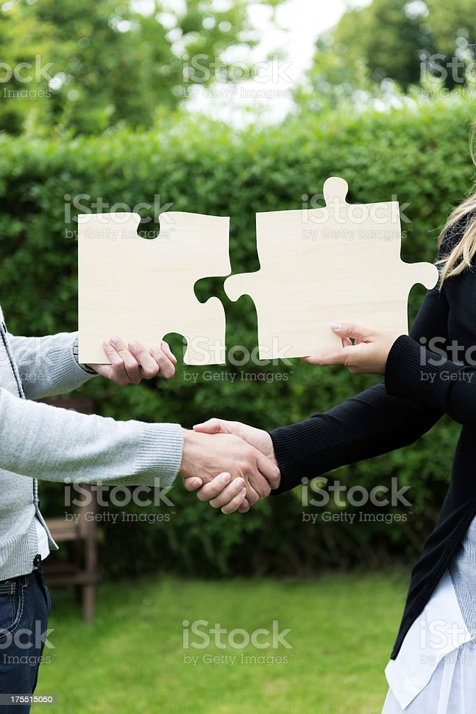 Handshake and two jigsaw puzzles seal a business deal royalty-free stock photo