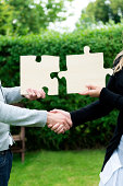 istock Handshake and two jigsaw puzzles seal a business deal 175515050