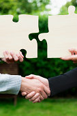 istock Handshake and two jigsaw puzzles seal a business deal 471437307