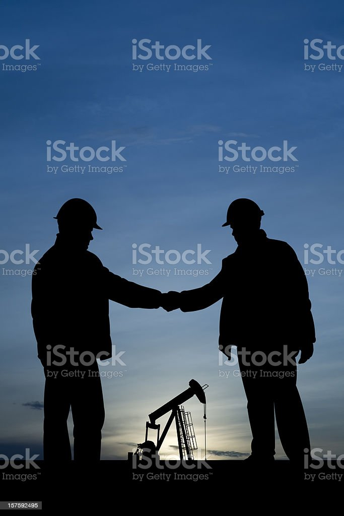 Handshake at a Pumpjack royalty-free stock photo